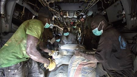 Resources are offloaded from a plane to assist those with Ebola.