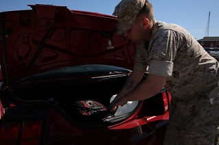 A Marine loads his vehicle emergency kit into his car.