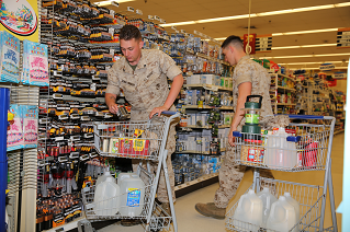 Two Marines shop in the commissary for emergency kit items in this image.