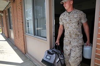 A Marine carries his 'Go Bag' out of the barracks.