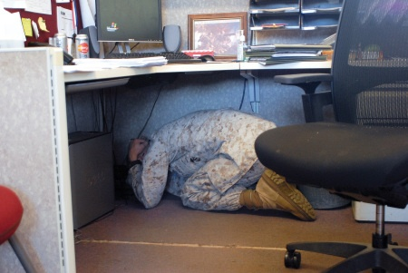 A Marine takes shelter beneath a desk in this image.