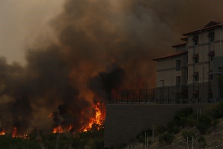 A wildfire threatens a home in this image.