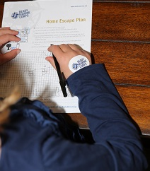 A young girl completes the home escape plan worksheet.