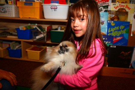 A young girl holds a dog in this image.