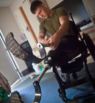 A wounded Marine affixes a prosthetic leg in this image.