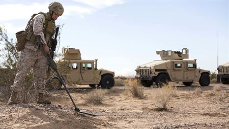 A Marine sweeps for explosive devices in this image.