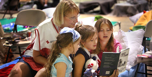 A Red Cross worker sits with three girls as they read a book in a shelter.