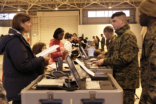A woman presents personnel with her NEO package in a NEO processing center.