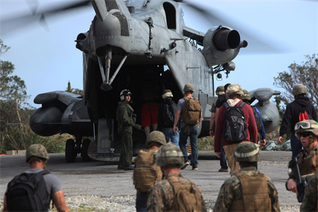 Marines assist noncombatants board an aircraft during an evacuation.
